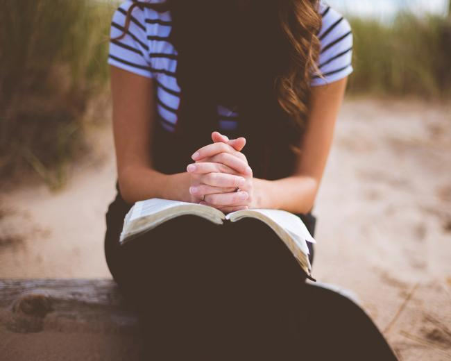 Photo of young woman praying with hands clasped together